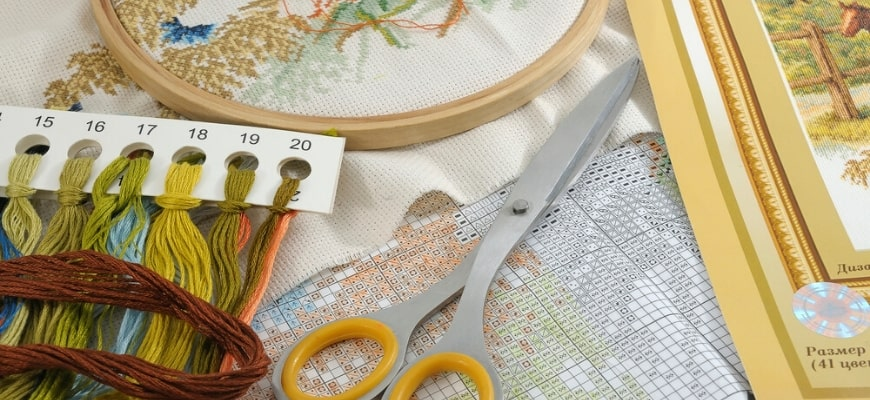 Scissor,threads,guide and embroidered cloth clutch on loop.