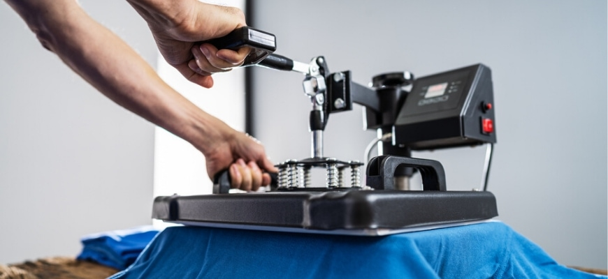 Close up shot of hands holding a heat press,applying pressure on a blue t-shirt