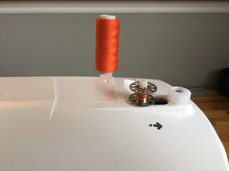 orange thread inserted into the one hole of the bobbin