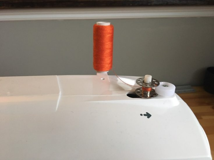 wrapping the orange thread around the center of the bobbin