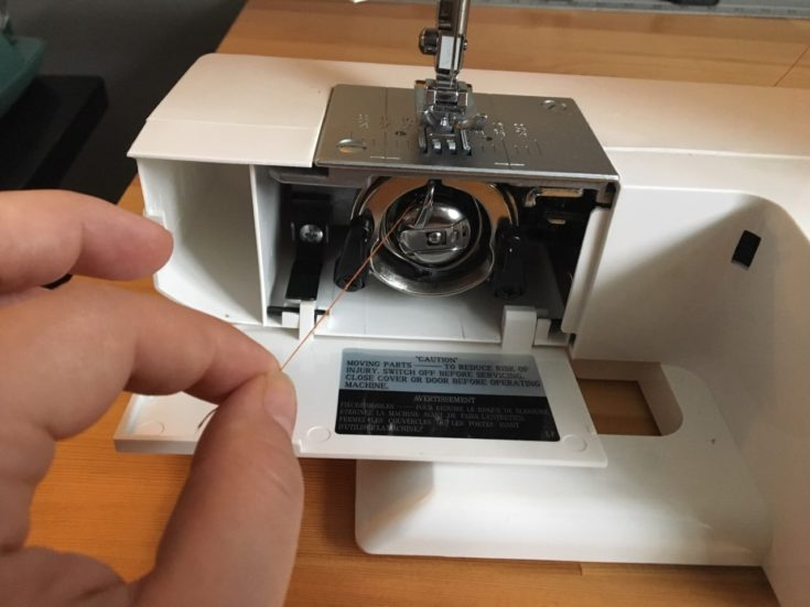 a person's hand grabbing the loose end of the bobbin's thread and pull it two or three inches