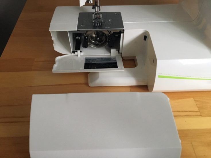 a sewing machine with an opened bobbin area on the top of the table