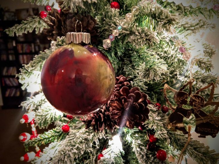 Close up shots of a christmas ball hanging on a christmas tree.