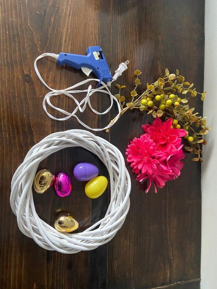 Twig Wreath + Plastic Easter eggs + Ribbon + Flowers + Leaves + Glue gun + Glue sticks