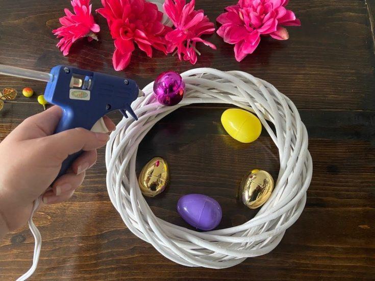 Plastic easter egg glued to white twig wreath.