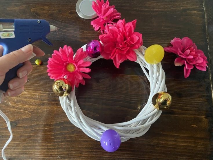 Plastic flowers and easter egg glued alternately to white twig wreath.