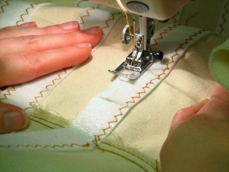 Close up shot of woman's hand sewing a layer of interface for hem.