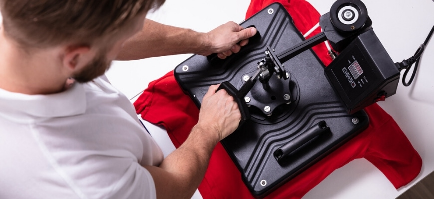 Top view of man pressing a heat press to red t-shirt.