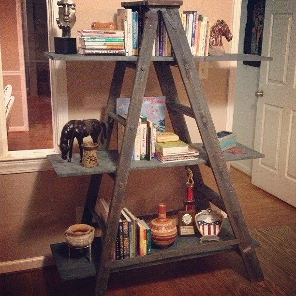 Wood ladder with plank in between steps a horse figurine in the second shelve