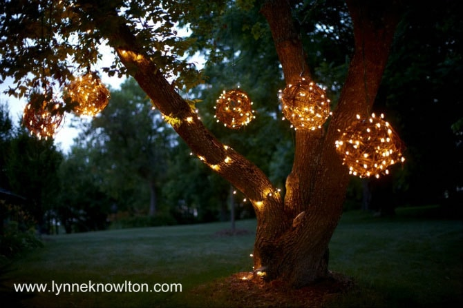 DIY Lynne Knowlton lighted grapevine balls hanging up on a tree