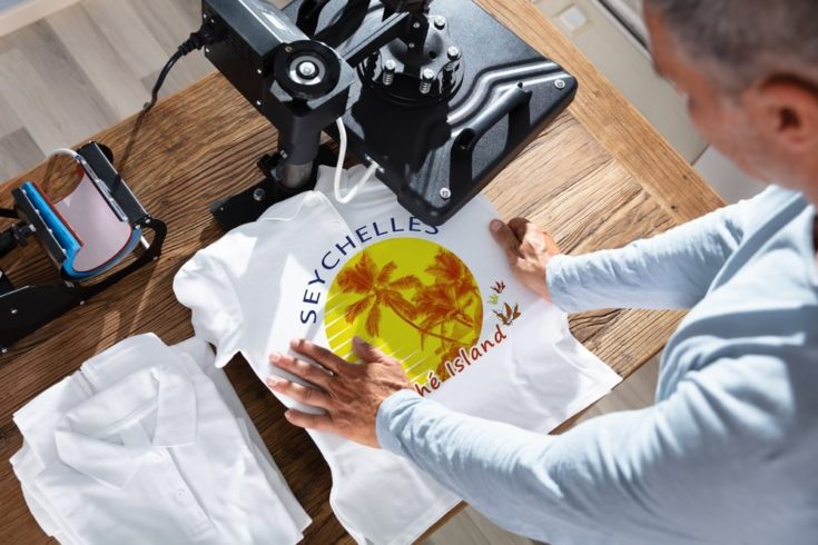 Man Printing Image On a white T-Shirt using a heat press machine