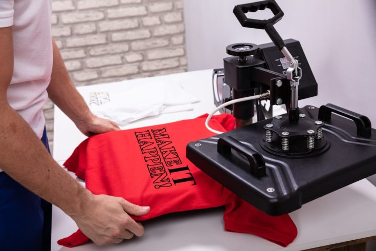 Man printing on a red t shirt in workshop using heat press machine