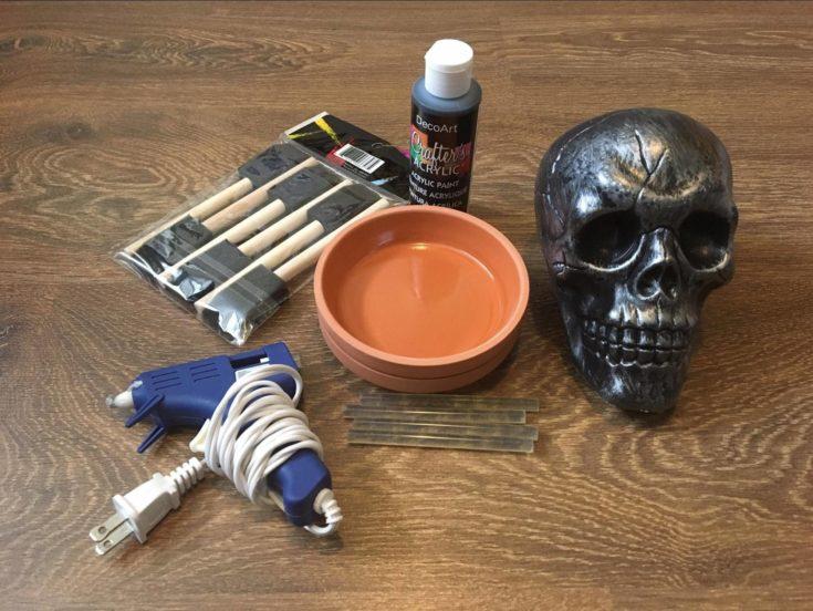 Glue gun + terra cotta + paint + paint brush + plastic skull + glue sticks on the wooden table