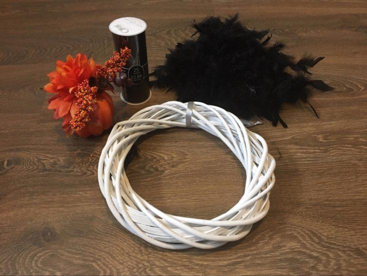 wreath + pumpkin decoration + black feather boa + black fabric
