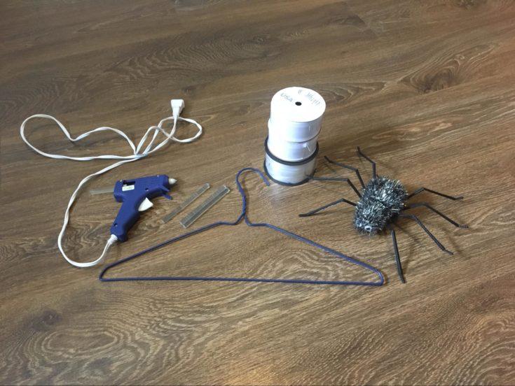Glue gun + wire hanger + white ribbon + plastic spider + glue sticks on the wooden table
