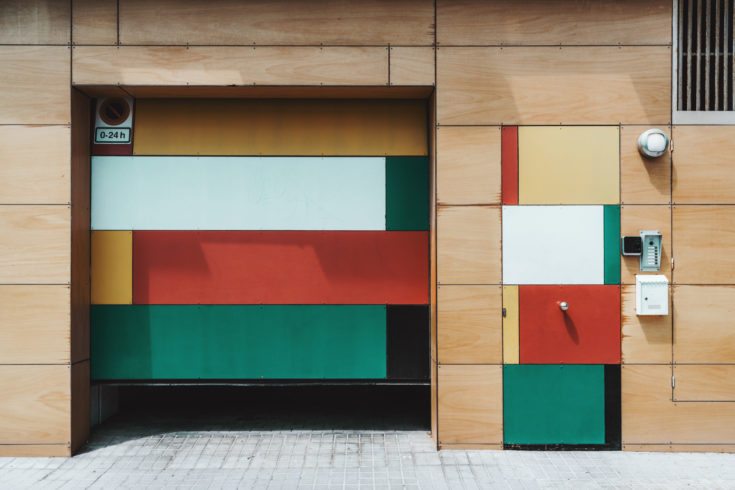 Multicolored fancy wooden facade of an ordinary house on a street of Barcelona: partly opened garage door, smaller entrance door with intercom and mailbox near