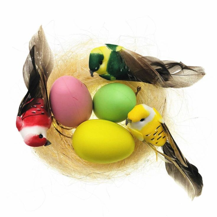 Brightly colored plastic eggs set on nest with birds on it's side.