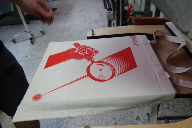 Final output of silk screen printing of magnifying glass reflection on a tote bag.