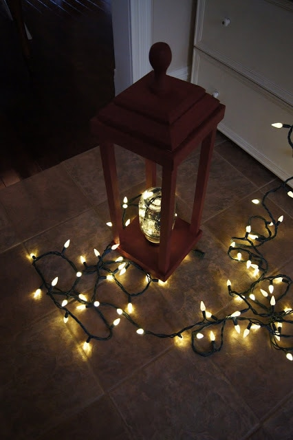 Old fashion Christmas lantern with Christmas lights on the floor