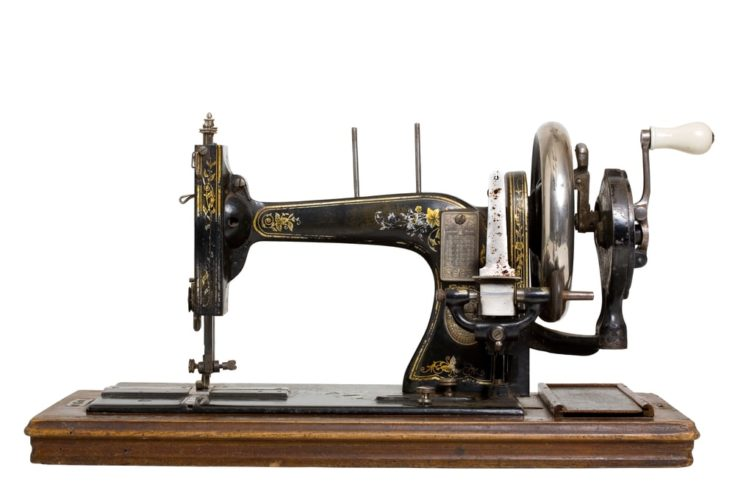 An old sewing machine on a wooden platform with a white background.