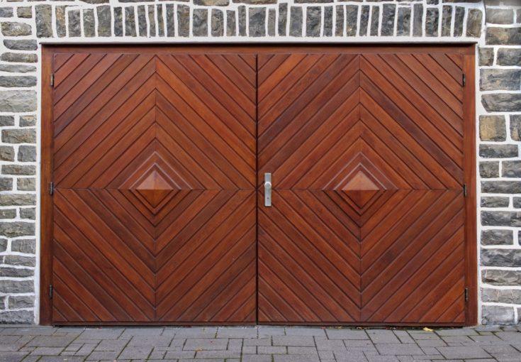 Old gray stone wall with double-leaved wooden herringbone garage door
