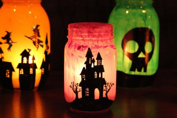 Jar luminaries painted inside with colors and designs for halloween.
