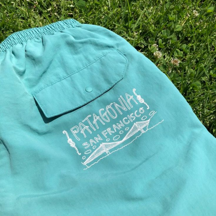 a cyan colored pants on a grass with patagonia san francisco print on it