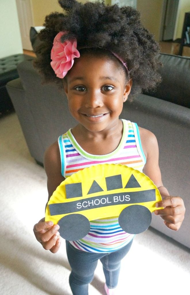 Pattern Practice - Young girl holding a school bus craft using a paper plate.