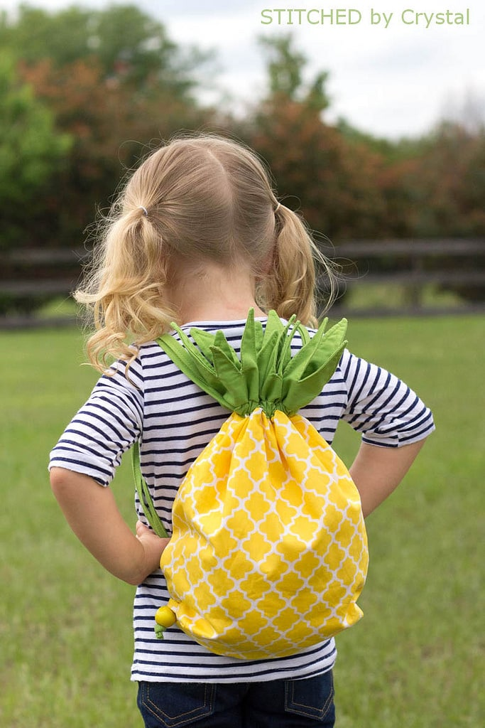 a little girl with Pineapple Drawstring Backpack