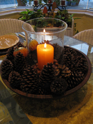 Orange candle surrounded by pinecone centerpiece