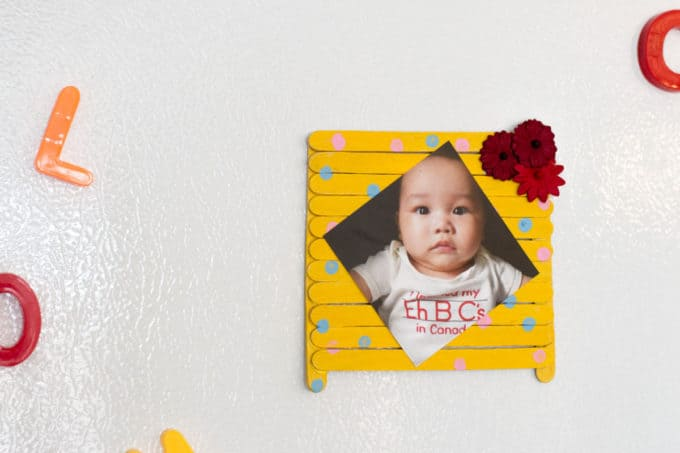 Popsicle Stick Photo Frame on white wall.