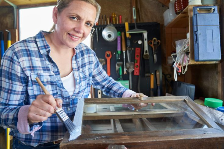 Portrait Of Mature Woman Upcycling Furniture In Workshop At Home Painting Cabinet