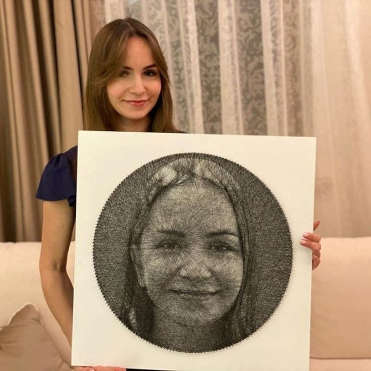 Young woman holding her portrait made by a string art.