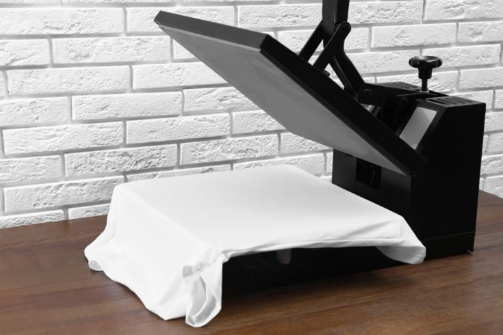 Heat press machine with t-shirt on wooden table near white brick wall