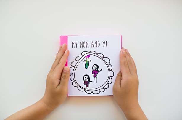 Woman's hand holding a Printable Mother's Day Book.