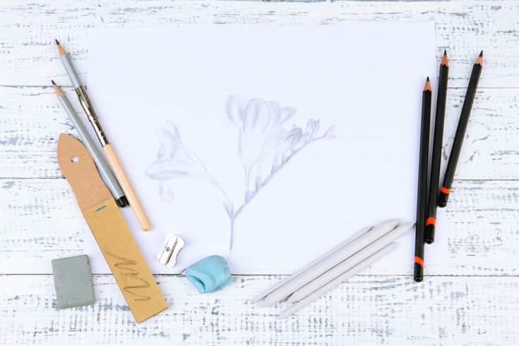 Professional art materials and sketch, on wooden table
