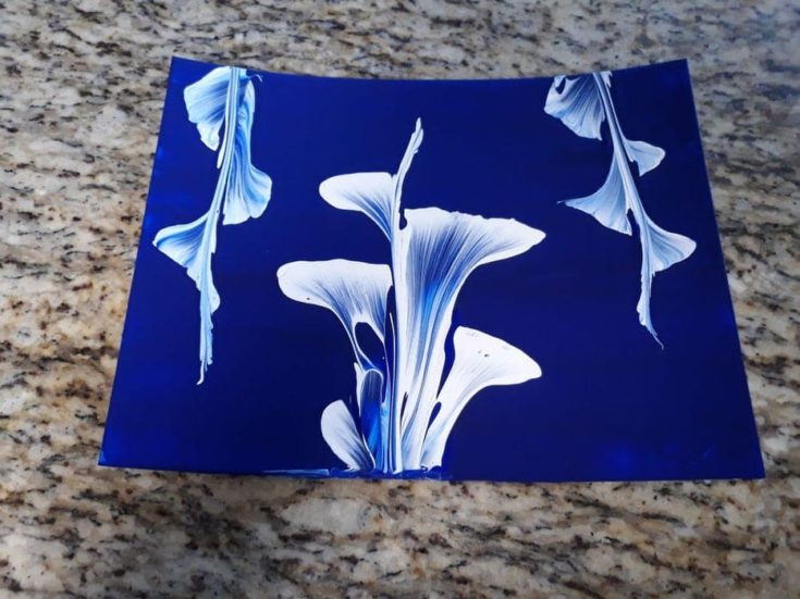 White flower on a blue canvass using a pull-string art.