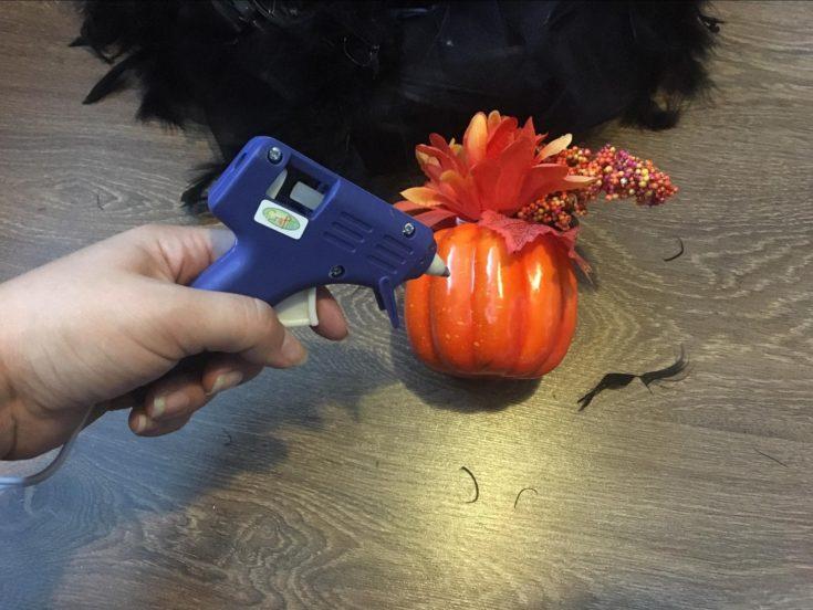 a hand holding a glue gun pointing to a plastic orange pumpkin