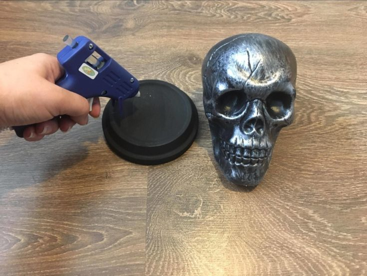 Putting glue on terra cotta saucer using a glue gun with plastic skull on the side