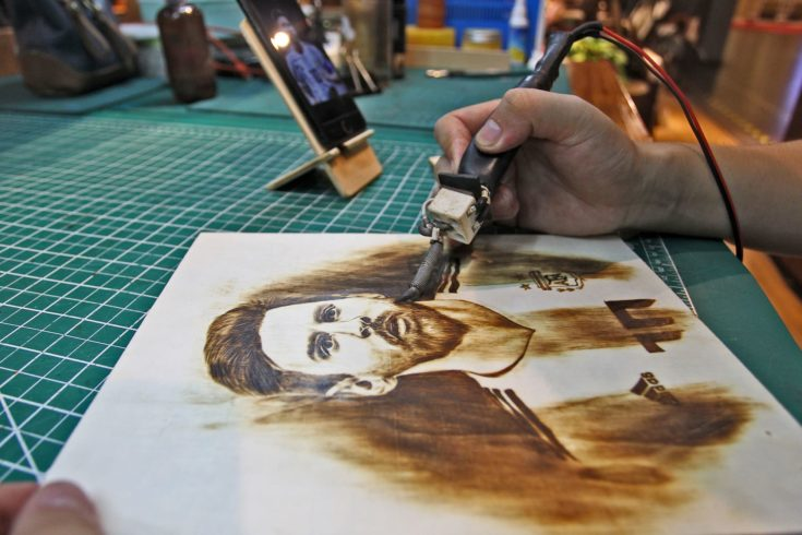 27-year-old Chinese man Peng Fang works with an art work of pyrography at his shop in Xi'an city, northwest China's Shaanxi province, 23 July 2018.