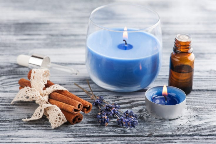 SPA composition with essential oil, lavender flowers, lit candles. Wooden background