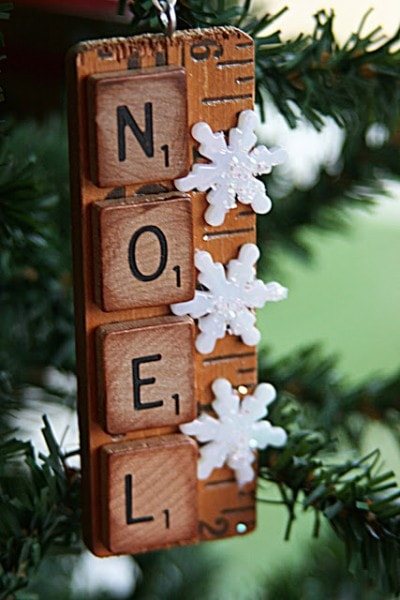 NOEL spelled with scrabble pieces pasted on a ruler with snowflakes ornament