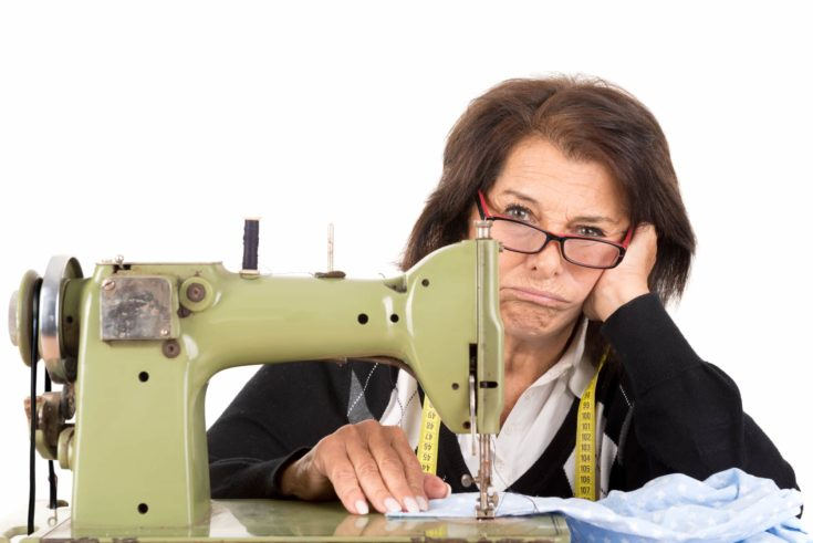 Stressed senior woman with sewing machine isolated in white