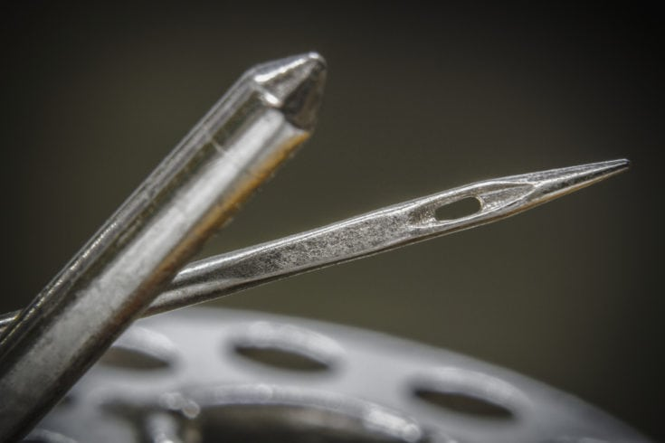 Sewing machine needles and thread metal reel close-up
