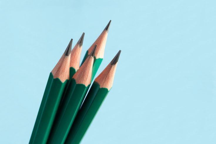 Few of classic graphite sharply sharpened pencils, in green wooden shell, on blue background.