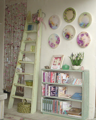 shabby chic ladder in light green besides a bookself