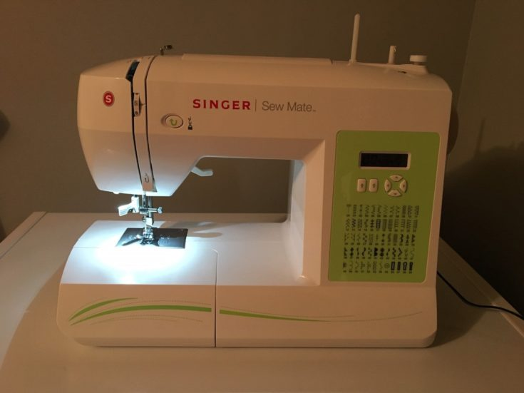 a white Singer Sew Mate sewing machine on the top of the table