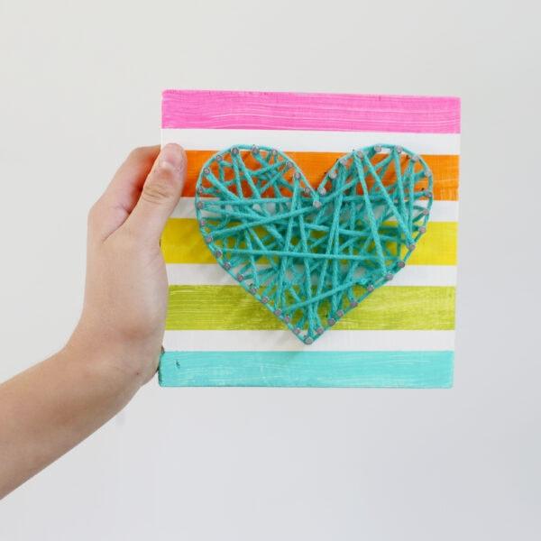 a hand holding String Art Heart Kids Craft