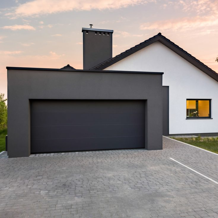 Stylish house with garage and cobblestone driveway, outdoors