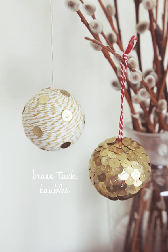 Ornament ball covered in brass tack the other is covered in yarn hanging on twigs